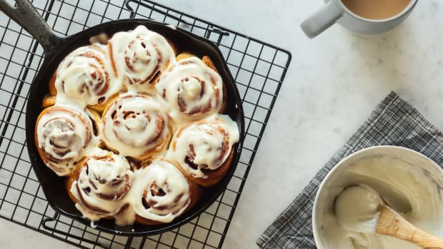 Homemade cinnamon rolls or buns baked in a cast iron skillet and covered with cream cheese icing. The skillet is cooling atop a black wire cooling rack on a white and gray marble countertop. A mug of coffee or tea is on the side next to a bowl full of icing.