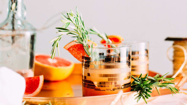 cocktail tumbler with squeeze of grapefruit on the rim with a rosemary sprig in the glass