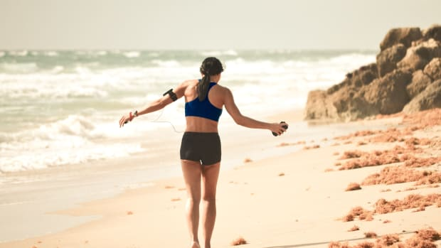 Girl walking on beach listening to music