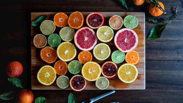 cut citrus, oranges, grapefruit, lime, lemons on cutting board