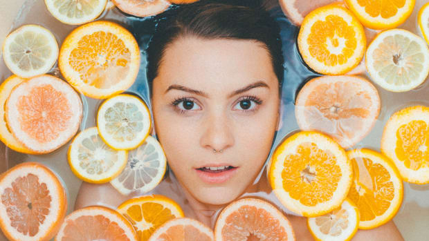 woman in tub surrounded by round citrus slices