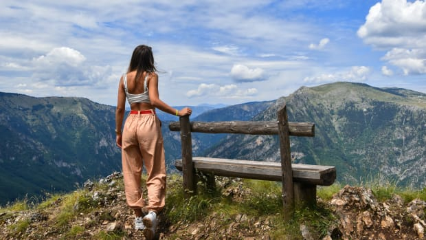 woman standing at top of mountain next to bench
