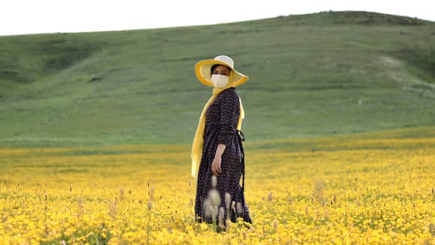 woman standing in field with yellow flowers wearing COVID-19 face mask in Ardabil Privince, Iran