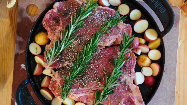 porterhouse steaks on grill pan with potatoes and rosemary
