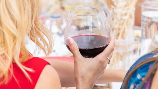 blonde woman holding glass of red wine