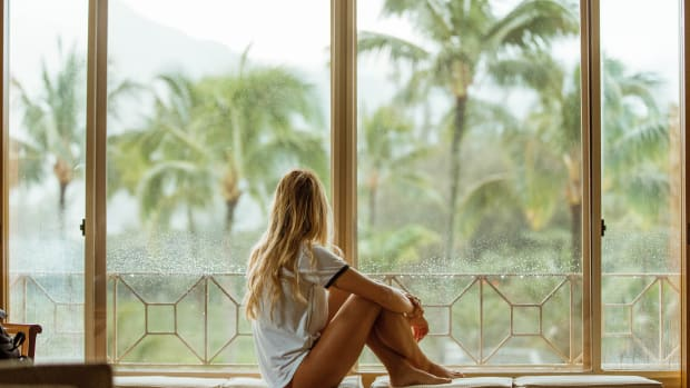 woman sitting at the window looking out at palm trees