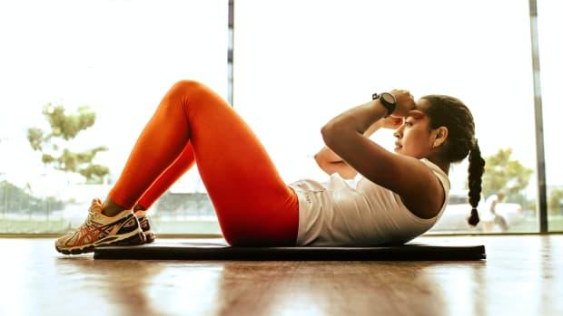 woman doing sit ups on mat indoors