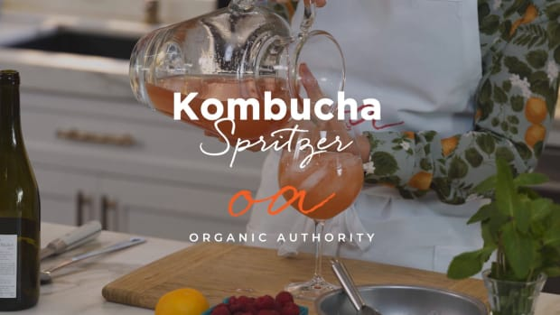 Woman pouring pitcher of kombucha spritzers into wine glass.