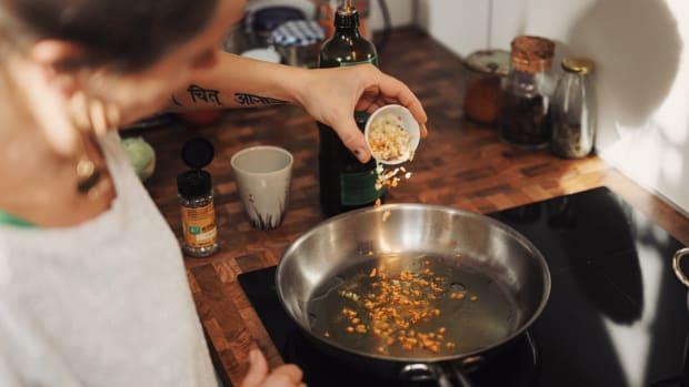 Woman pouring chopped garlic into saute pan.