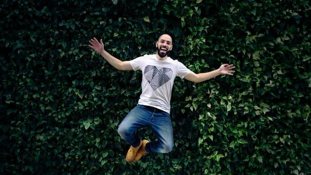 man jumping up and kicking his heals against a green wall.
