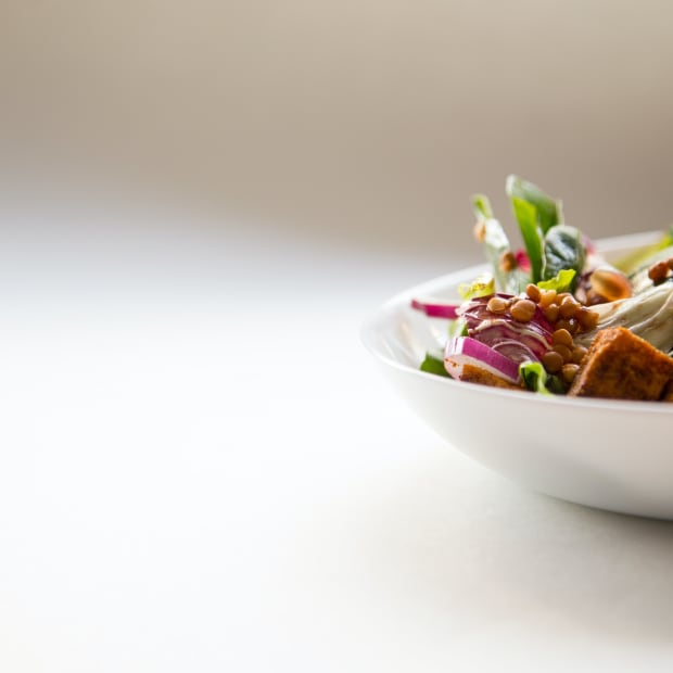 salad in a white bowl against white background