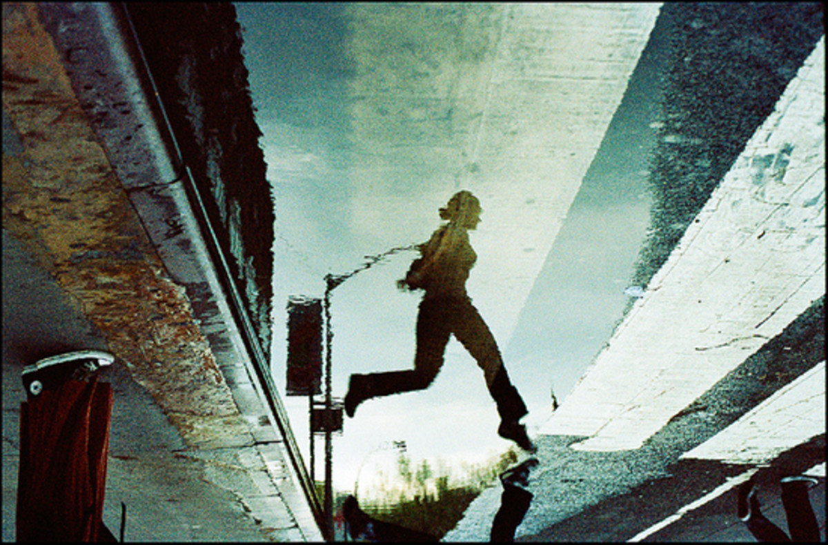 Woman jumping over puddle