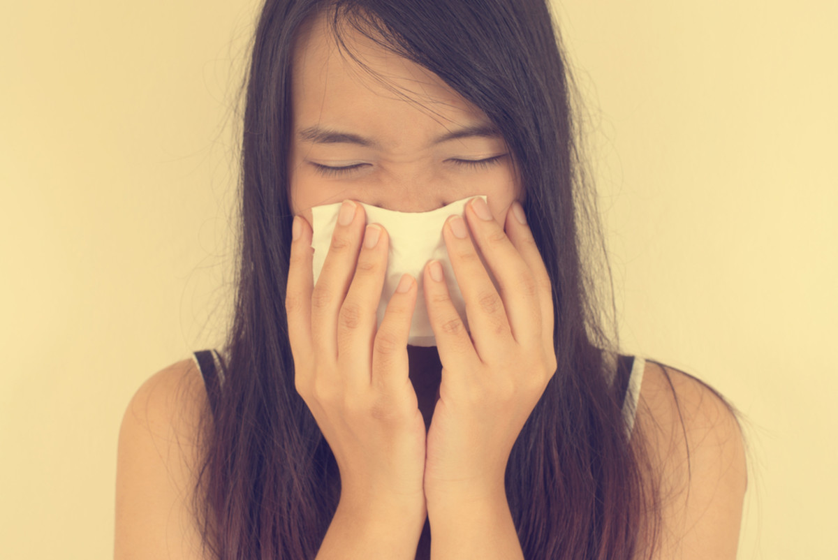 woman covering her nose with a tissue