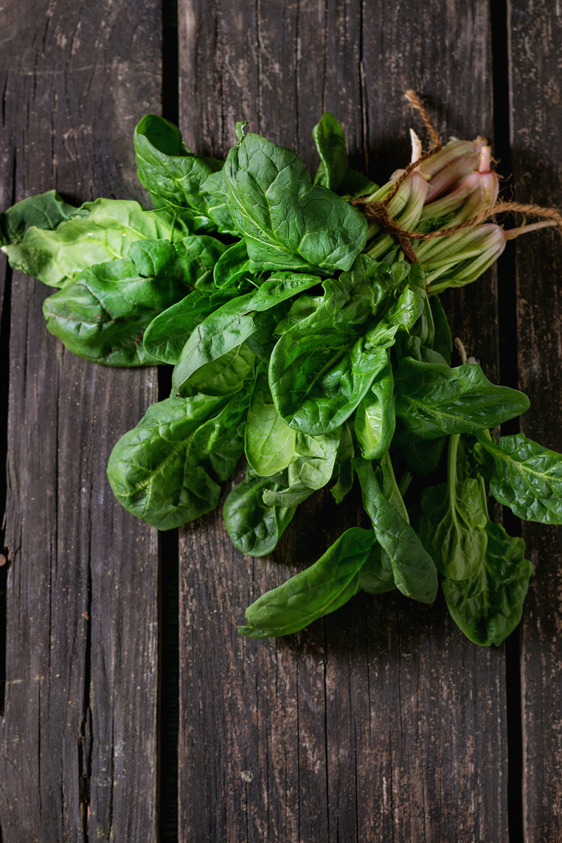 Spinach with twine on wood board