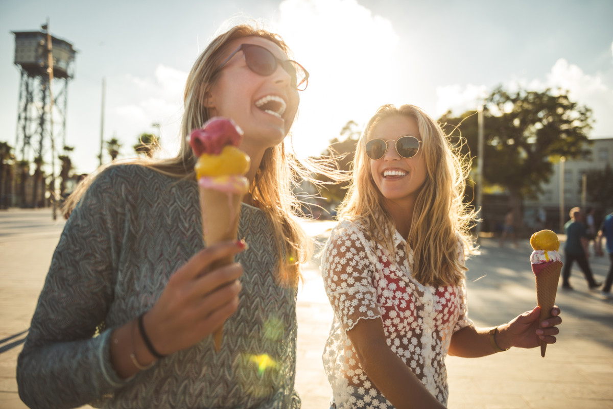 Two women enjoying summer holiday walk and eating an ice cream.