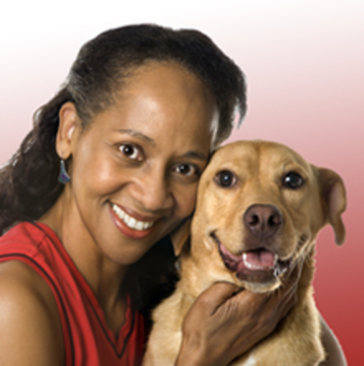 Woman holding dog and smiling.