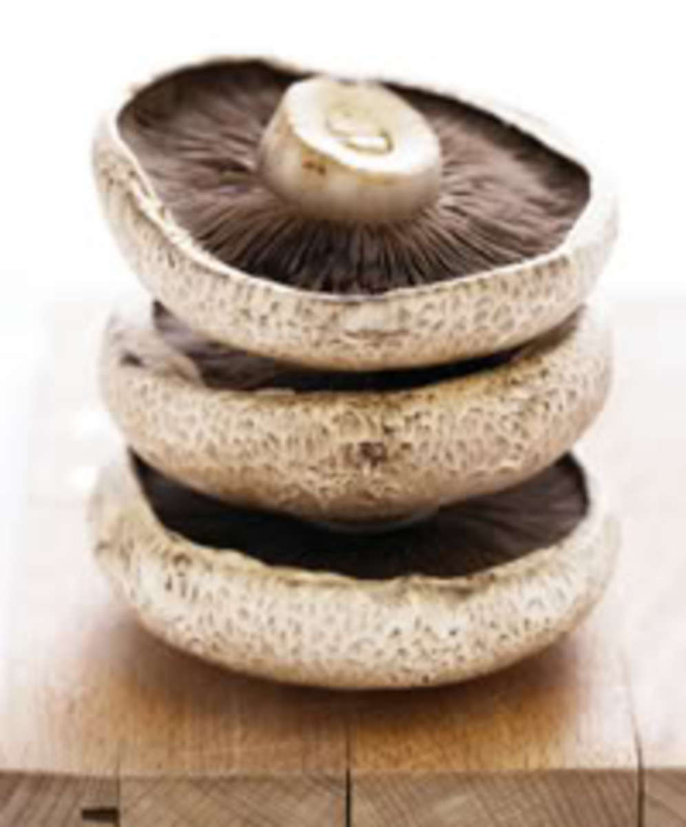 Three flat mushrooms in pile on wooden board, close-up