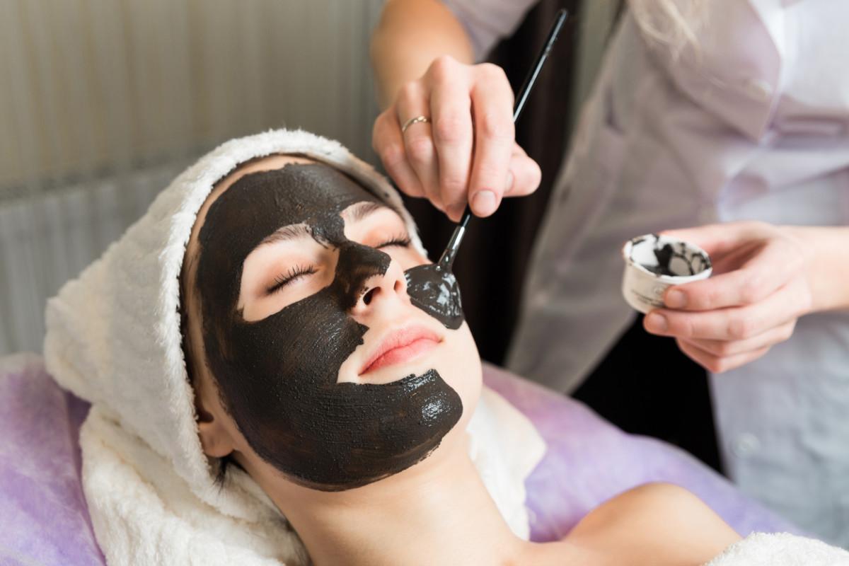 skin care, beautician applying face mask cream