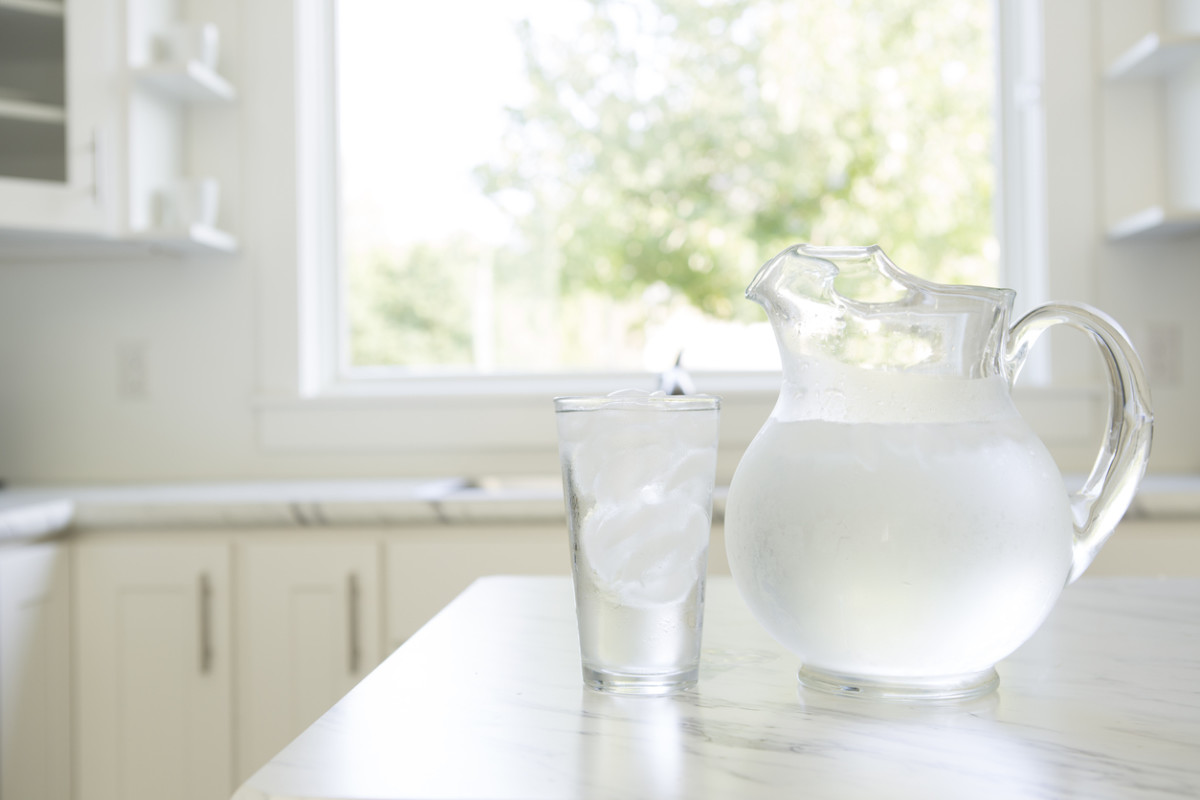A water pitcher and glass on a kitchen countertop