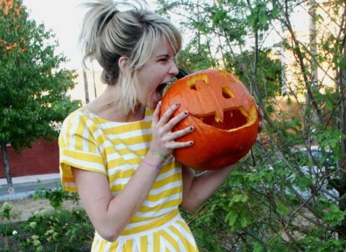 Girl bites pumpkin