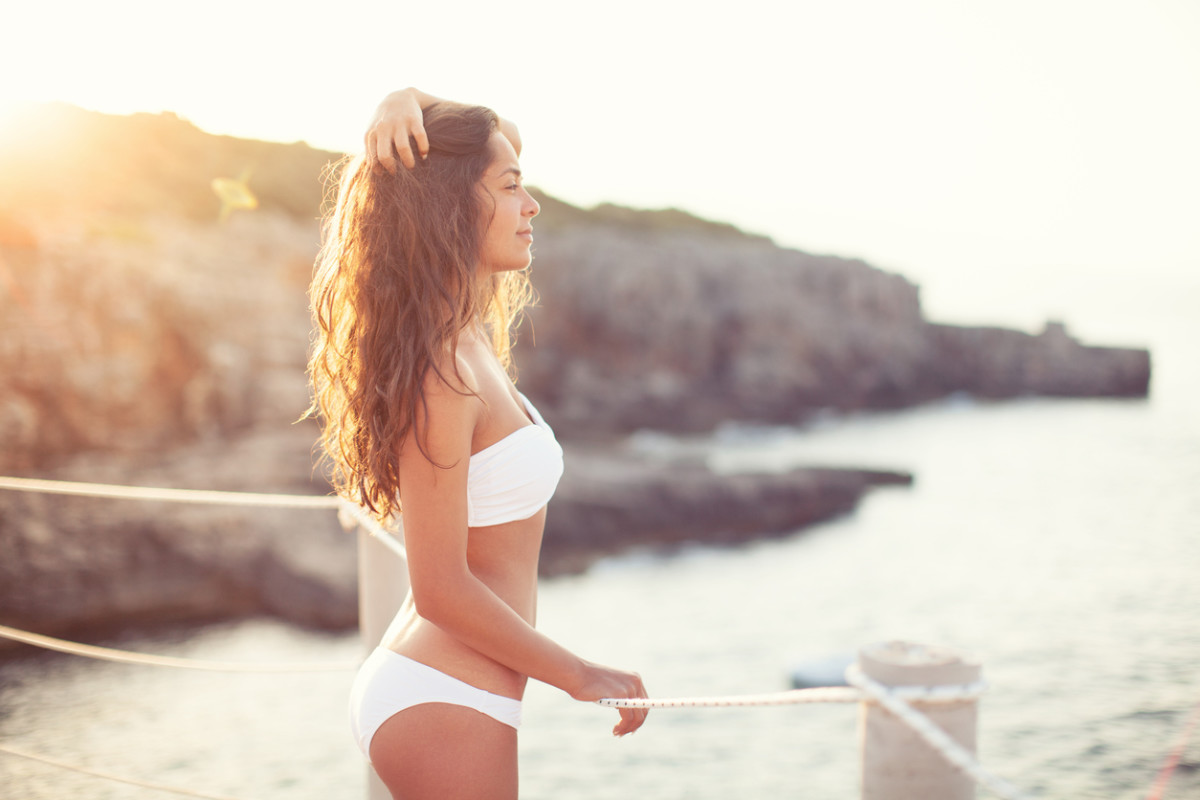 Pretty girl standing in white bikini on a terrace by the sea and enjoying in morning sunlight. She is beautiful, with long brown hair and tight body.