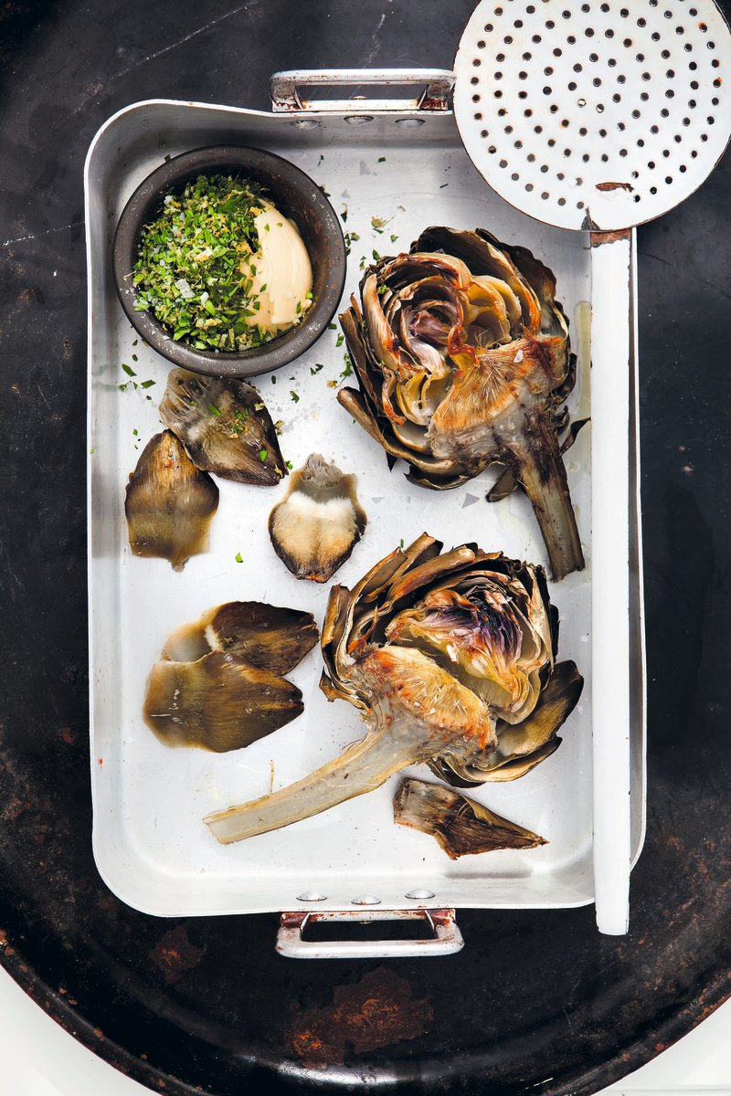 grilled artichokes, butter, herbs on a tray