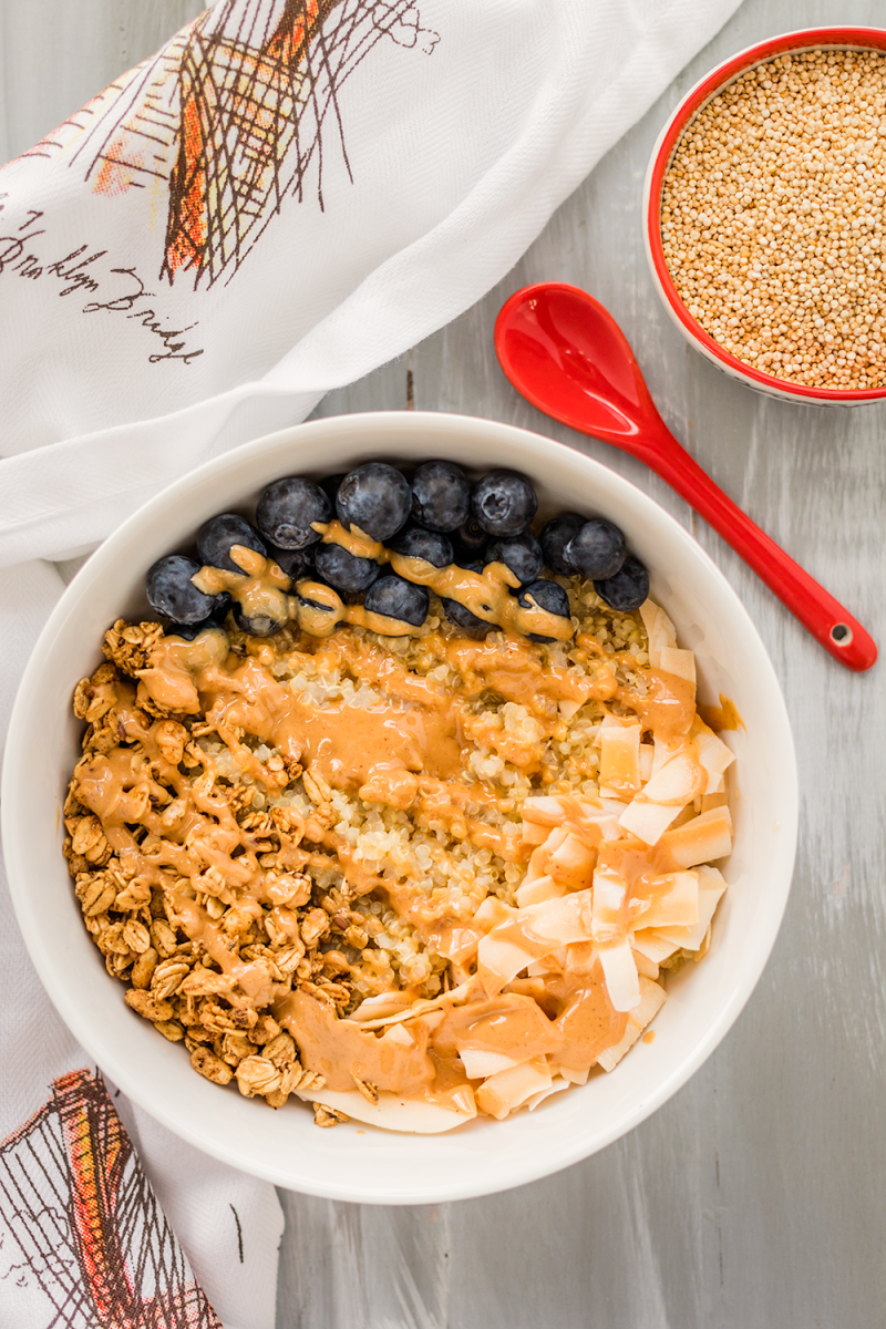 Vegan and gluten-free quinoa breakfast bowl with peanut butter, blueberries, and coconut flakes