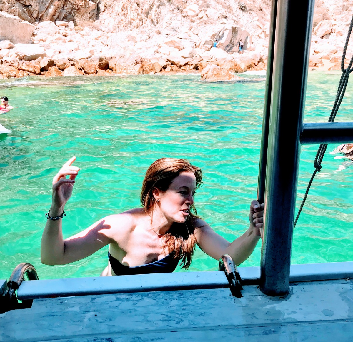 Laura dipping in the water off the Arch of Cabo San Lucas.