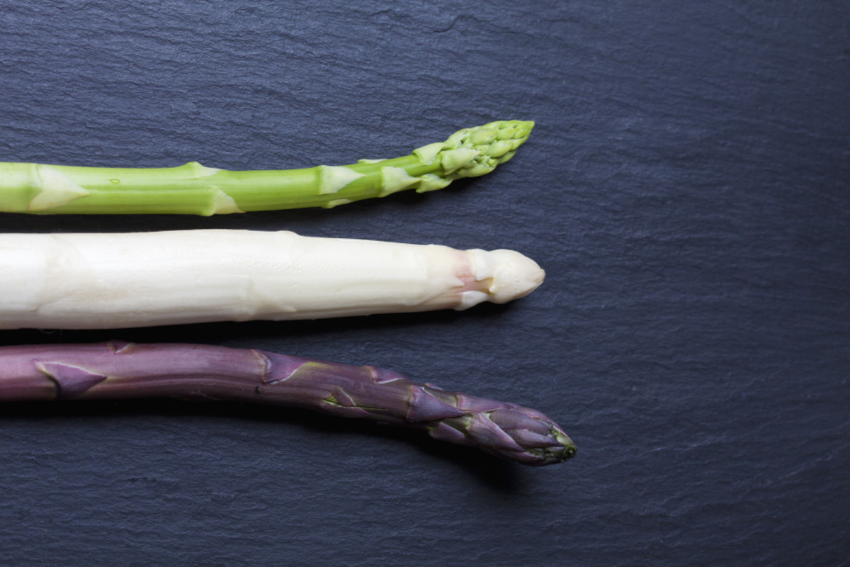 Image of green, white, purple asparagus on slate via Shutterstock