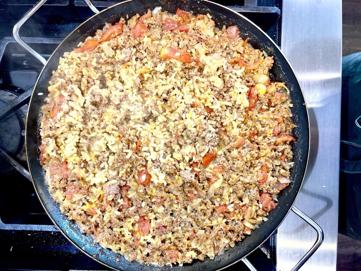 Paella rice and soffrito in pan on stove top.