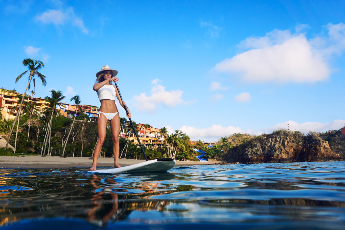 Woman stand up paddle boarding in the calm waters off of Costa Careyes, Mexico.